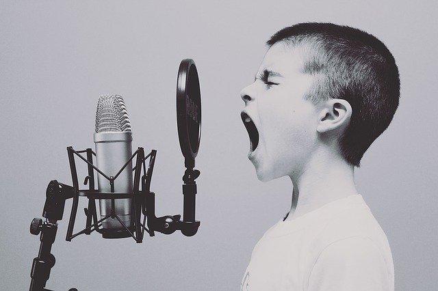 Avere talento - bambino che urla contro un microfono da studio di registrazione